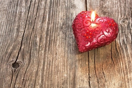 12537949 - red heart shaped candle on wooden background