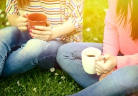 40251740 - young women drinking coffee at park and enjoying summer day
