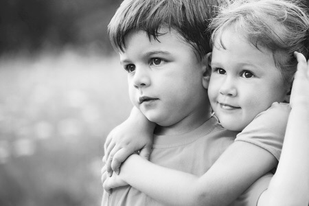10656936 - portrait of a cheerful girl and boy hugging fun in outdoor