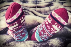 44715360 - female legs in christmas socks under a blanket of fur. toning image